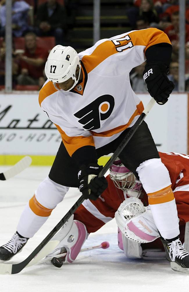 Detroit Red Wings goalie Jimmy Howard, bottom, stops a shot by Philadelphia Flyers right wing Wayne Simmonds (17) during the first period of an NHL hockey game in Detroit, Saturday, Oct. 12, 2013