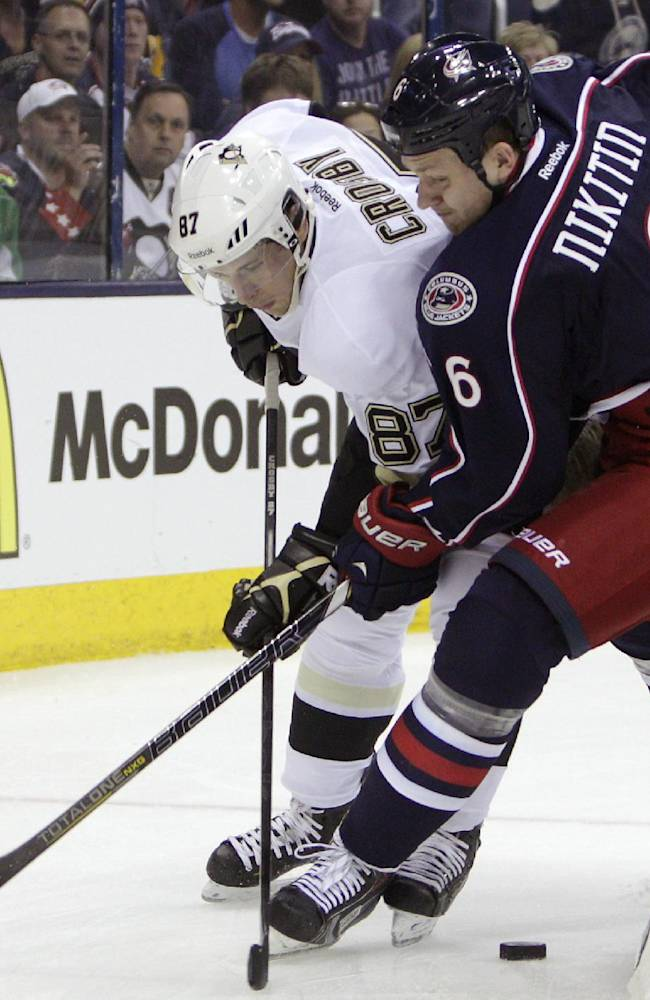Pittsburgh Penguins' Sidney Crosby, left, and Columbus Blue Jackets' Nikita Nikitin, of Russia, fight for a loose puck during the first period of a first-round NHL playoff hockey game Monday, April 21, 2014, in Columbus, Ohio