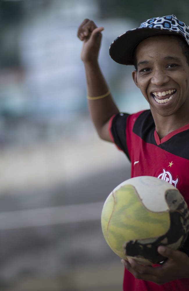 Kelvin, 15,  poses for a photo before playing soccer at the Sao Carlos slum in Rio de Janeiro, Brazil, Monday, May 12, 2014. As opening day for the World Cup approaches people continue to stage protests, some about the billions of dollars spent on the World Cup at a time of social hardship, but soccer is still a unifying force. The international soccer tournament will be the first in the South American nation since 1950