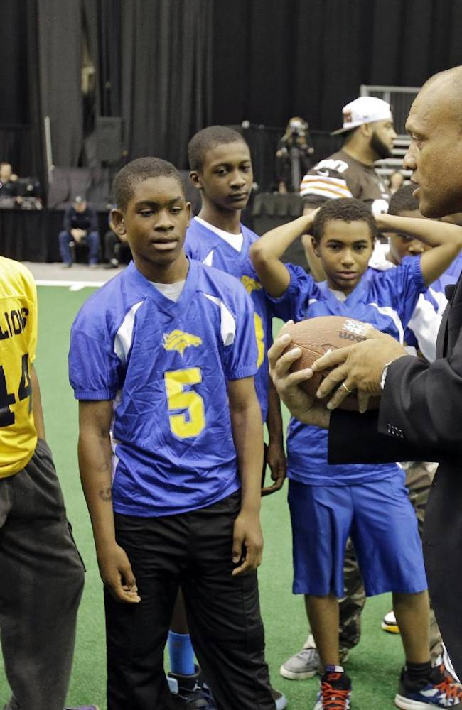 Newly-elected Hall of Famer Aeneas Williams, right, instructs youth league players during a punt, pass and kick competition at the inaugural Pro Football Hall of Fame Fan Fest Saturday, May 3, 2014, at the International Exposition Center in Cleveland