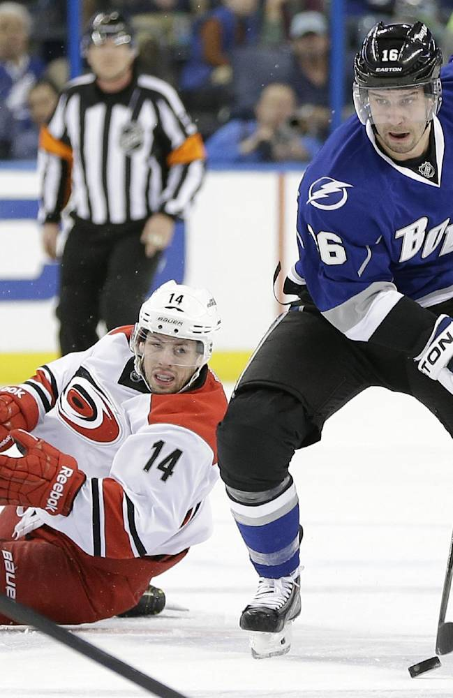 Tampa Bay Lightning right wing Teddy Purcell (16) skates through the neutral zone after Carolina Hurricanes left wing Nathan Gerbe (14) fell down during the second period of an NHL hockey game, Saturday, Dec. 21, 2013, in Tampa, Fla