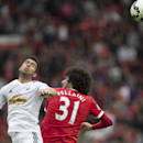 Manchester United's Marouane Fellaini, right, fights for the ball against Swansea City's Jordi Amat during their English Premier League soccer match at Old Trafford Stadium, Manchester, England, Saturday Aug. 16, 2014