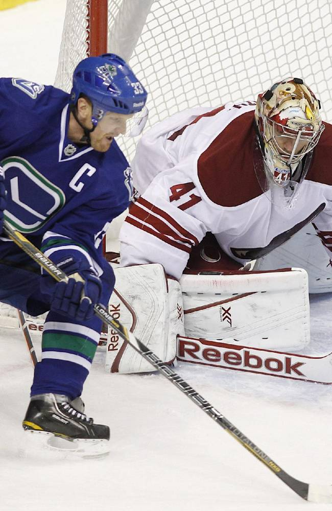 Phoenix Coyotes goaltender Mike Smith (41) makes a save against Vancouver Canucks' Henrik Sedin (22) during third period NHL hockey action in Vancouver, British Columbia, on Friday Dec. 6, 2013