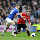 Everton's John Stones, left, and Manchester United's Wayne Rooney battle for the ball during their English Premier League soccer match at Goodison Park in Liverpool, England, Sunday April 20, 2014