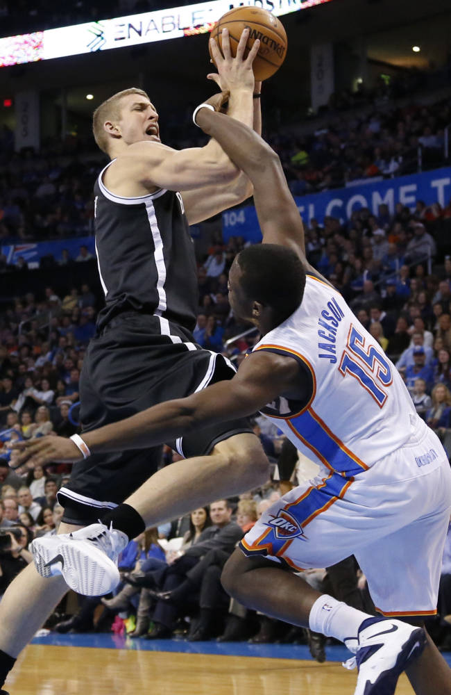 Brooklyn Nets forward Mason Plumlee is fouled by Oklahoma City Thunder guard Reggie Jackson (15) in the first quarter of an NBA basketball game in Oklahoma City, Thursday, Jan. 2, 2014