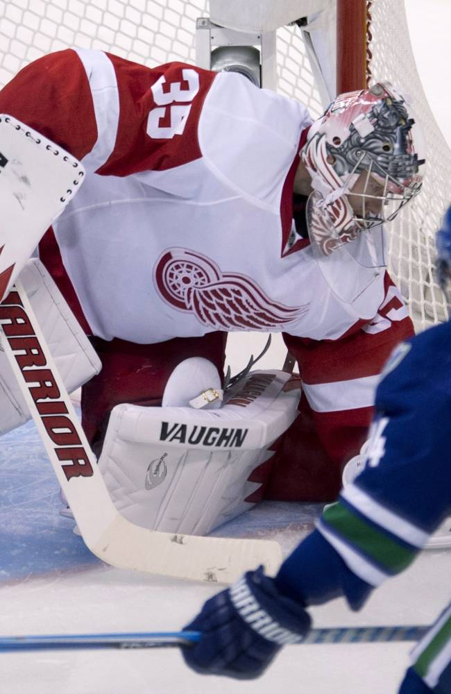 Detroit Red Wings goalie Jimmy Howard (35) stops a shot from Vancouver Canucks center Alex Burrows (14) during the second period of an NHL hockey game in Vancouver, British Columbia, Wednesday, Oct. 30, 2013