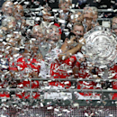 Arsenal's Mikel Arteta, centre, holds with teammates the English FA Community Shield as confetti falls after his team defeated Manchester City following the traditional season opening soccer match at Wembley Stadium, London Sunday, Aug. 10, 2014. Arsenal