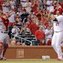 Cincinnati Reds catcher Devin Mesoraco stands near as St. Louis Cardinals' Jhonny Peralta claps his hands while crossing home plate after hitting a solo home run during the sixth inning of a baseball game Tuesday, Aug. 19, 2014, in St. Louis. (AP Photo/Scott Kane)