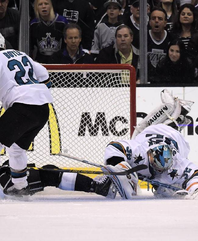 San Jose Sharks goalie Alex Stalock, right, stops a shot as Los Angeles Kings right wing Dustin Brown, lower left, falls and defenseman Dan Boyle looks on during the third period in Game 6 of an NHL hockey first-round playoff series, Monday, April 28, 2014, in Los Angeles. The Kings won 4-1. (AP Photo)