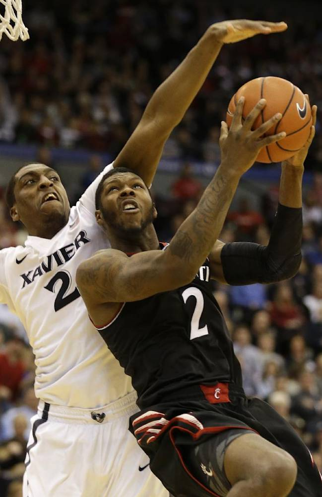 Cincinnati forward Titus Rubles, right, shoots against Xavier forward James Farr in the second half of an NCAA college basketball game, Saturday, Dec. 14, 2013, in Cincinnati. Xavier won 64-47