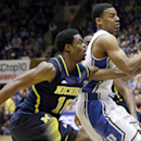 Duke's Quinn Cook, right, is pressured by Michigan's Derrick Walton Jr. (10) during the first half of an NCAA college basketball game in Durham, N.C., Tuesday, Dec. 3, 2013. (AP Photo/Gerry Broome)