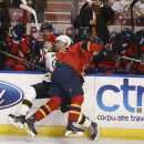 Boston Bruins' Johnny Boychuk (55) and Florida Panthers' Krys Barch (21) slam into the boards during the second period of an NHL hockey game in Sunrise, Fla., Sunday, March 9, 2014 The Associated Press