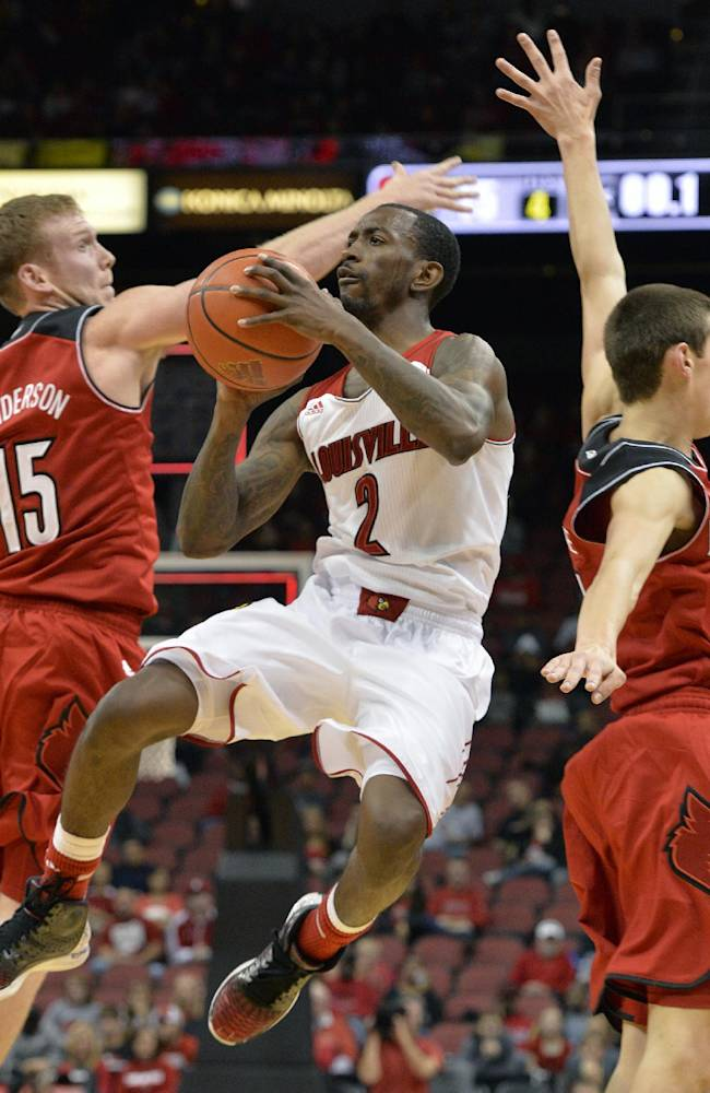 Louisville's Russ Smith, center, splits the defense of Tim Henderson, left, and Dillon Avare to attempt a shot during their NCAA college basketball scrimmage Saturday, Oct. 19, 2013, in Louisville, Ky