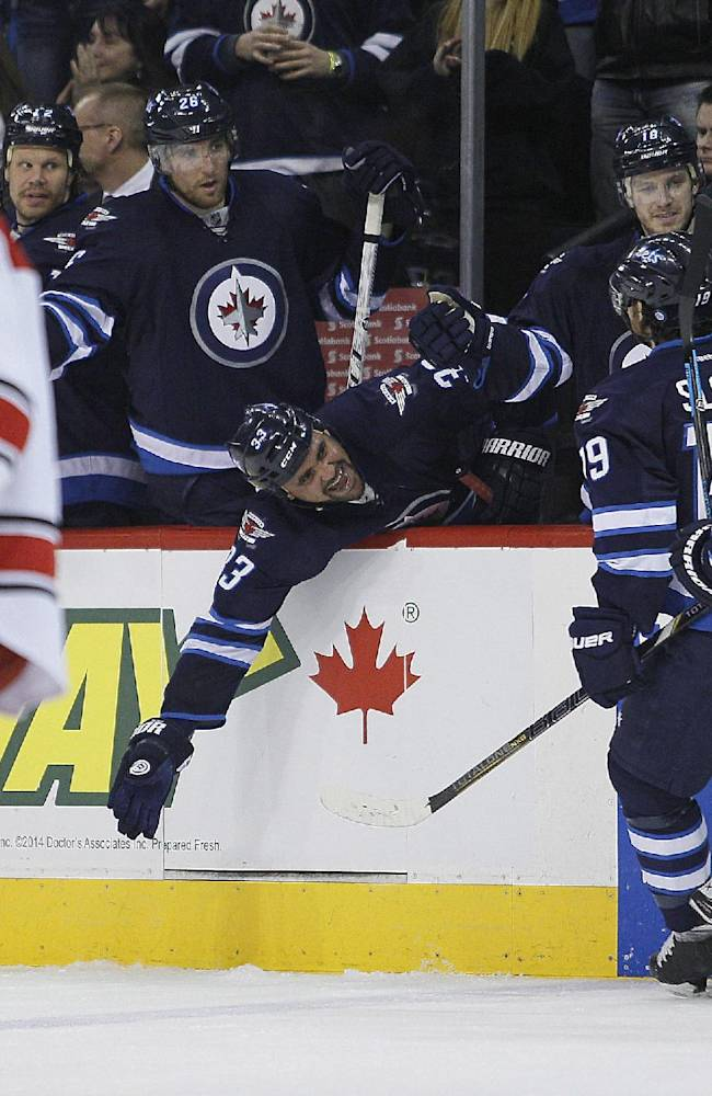 Winnipeg Jets' Dustin Byfuglien (33) celebrates after Jim Slater (19) tipped a shot past Carolina Hurricanes' goaltender Cam Ward during the second period of an NHL hockey game, Saturday, March 22, 2014, in Winnipeg, Manitoba