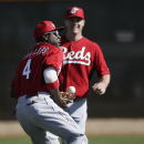 Cincinnati Reds second baseman Brandon Phillips, left, bobbles the ball while trying to make a catch as right fielder Jay Bruce watches during a spring training baseball workout Thursday, Feb. 20, 2014, in Goodyear, Ariz The Associated Press