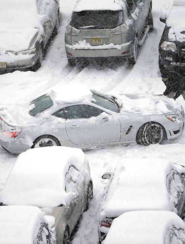 Snow-covered cars occupy a parking lot at Lincoln Financial Field during the second half of an NFL football game on Sunday, Dec. 8, 2013, in Philadelphia