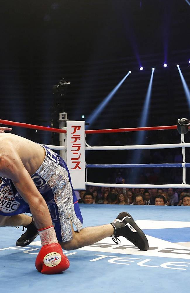 Japanese challenger Naoya Inoue, right, looks at Mexican champion Adrian Hernandez after knocking him down in the sixth round of their WBC light flyweight boxing title bout in Tokyo, Sunday, April 6, 2014. Inoue defeated Hernandez by a technical knockout to become the champion