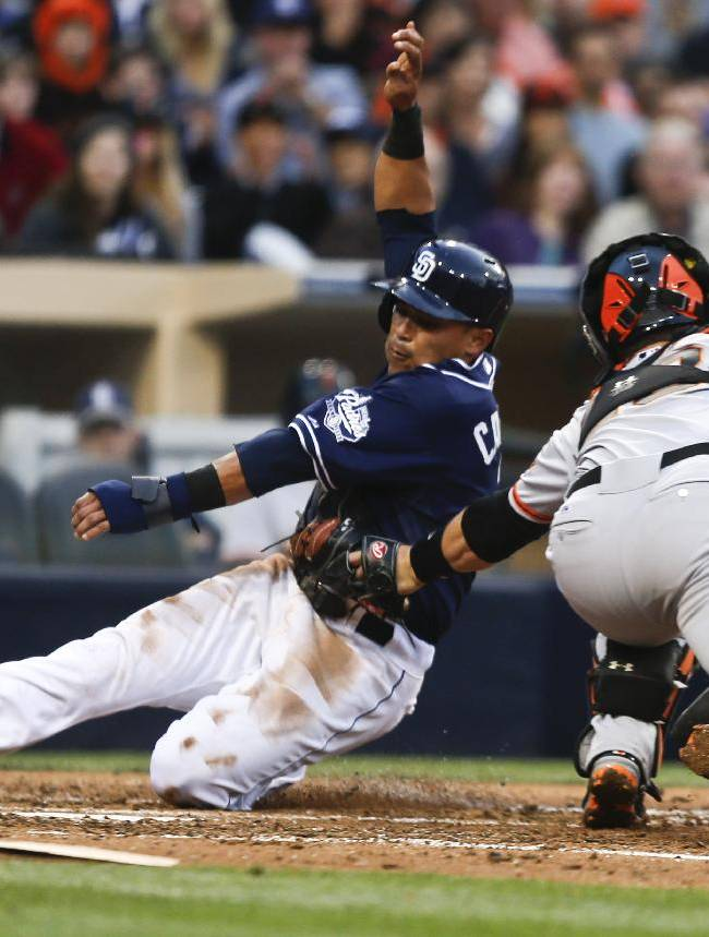 San Diego Padres' Everth Cabrera is out at home as San Francisco Giants catcher Buster Posey tags him in the fifth inning of a baseball game Saturday, April 19, 2014, in San Diego. Cabrera was trying to score from third on an infield grounder