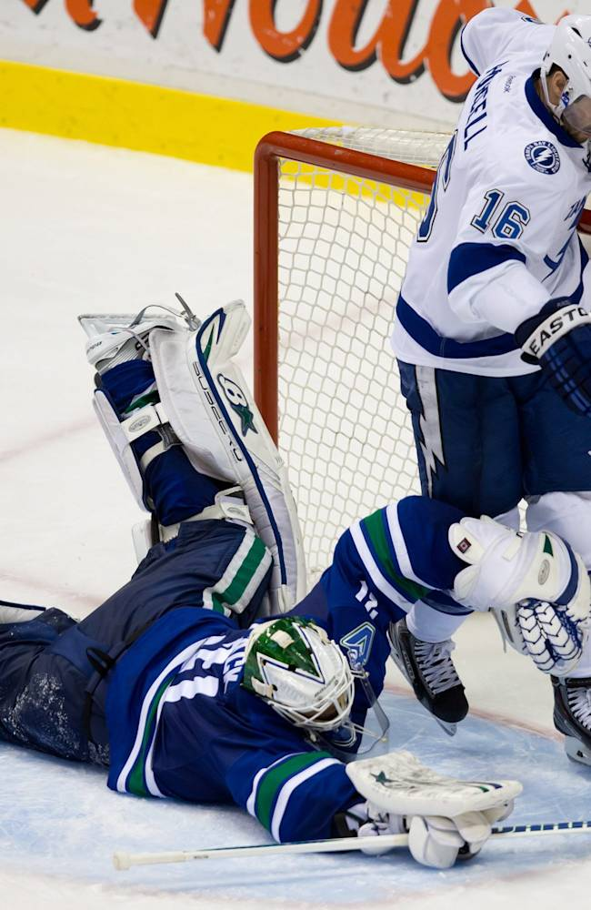 Vancouver Canucks' goalie Eddie Lack, left, of Sweden, lies on the ice after allowing a goal to Tampa Bay Lightning's Alex Killorn, not seen, as Teddy Purcell skates through the crease during an NHL hockey game Wednesday, Jan. 1, 2014, in Vancouver, British Columbia