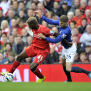 Liverpool's Mario Balotelli, left, is tackled by Everton's John Stones during their English Premier League soccer match at Anfield in Liverpool, England, Saturday Sept. 27, 2014.