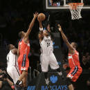 Brooklyn Nets' Paul Pierce puts up a shot between Washington Wizards' Kevin Seraphin, right, and Trevor Ariza during the first half of an NBA basketball game Wednesday, Dec. 18, 2013, in New York. (AP Photo/Seth Wenig)