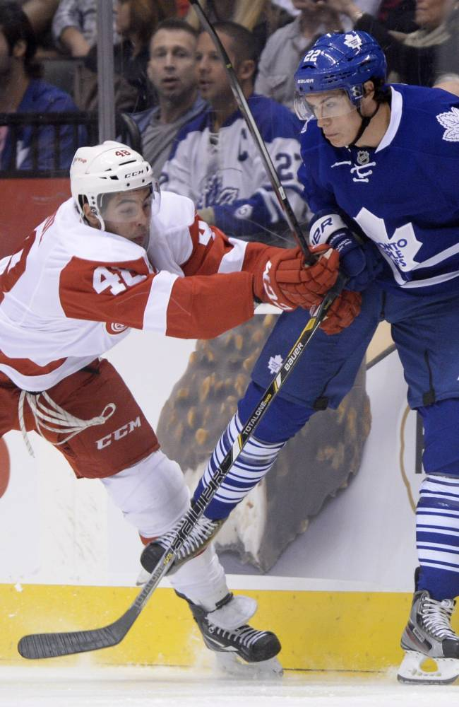 Toronto Maple Leafs' Joe Colborne, right, and Detroit Red Wings' Ryan Sproul battle along the boards during first-period preseason NHL hockey game action in Toronto, Saturday Sept. 28, 2013