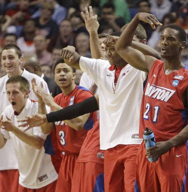 Dayton's Dyshawn Pierre (21) celebrates with teammates during the second half of a third-round game against Syracuse in the NCAA men's college basketball tournament in Buffalo, N.Y., Saturday, March 22, 2014