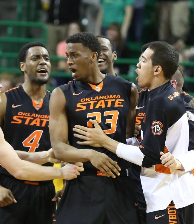 Oklahoma State players grab forward Leyton Hammonds (23) after sending their game against Baylor to overtime in an NCAA college basketball game, Monday, Feb. 17, 2014, in Waco, Texas.  Baylor won 70-64