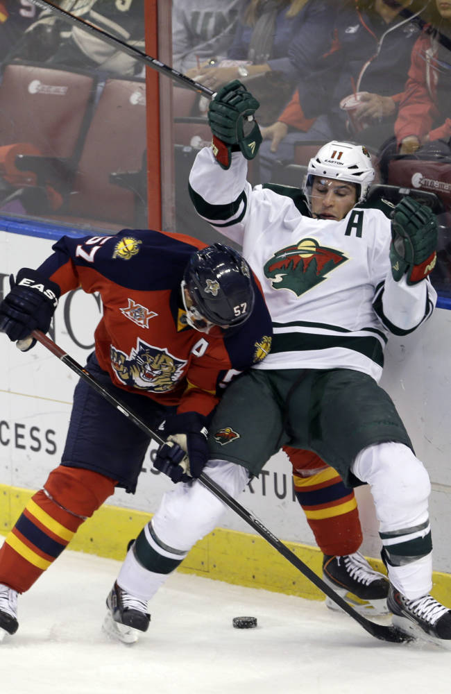 Florida Panthers center Marcel Goc (57) checks Minnesota Wild left wing Zach Parise, righ, in the third period of an NHL hockey game, Saturday, Oct. 19, 2013, in Sunrise, Fla