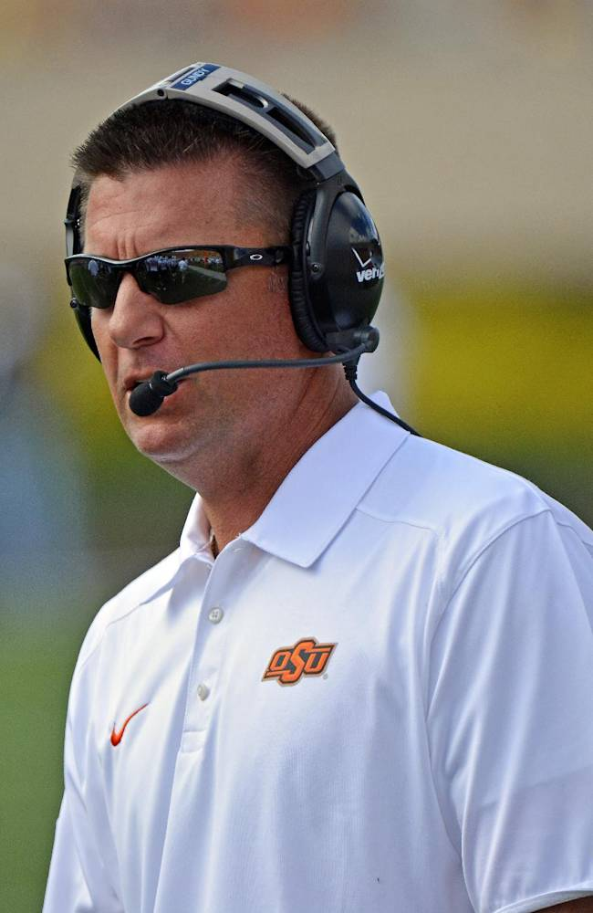 Oklahoma State coach Mike Gundy watches during in the fourth quarter of an NCAA college football game against West Virginia in Morgantown, W.Va., on Saturday, Sept. 28, 2013