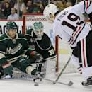 Minnesota Wild defenseman Keith Ballard, left, kicks away a shot by Chicago Blackhawks center Jonathan Toews (19) as Minnesota Wild goalie Josh Harding (37) covers the net during the second period of an NHL hockey game in St. Paul, Minn., Thursday, Dec. 5, 2013. (AP Photo/Ann Heisenfelt)