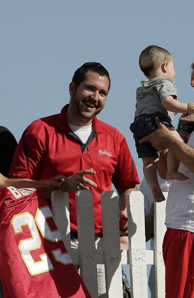 Kansas City Chiefs punter Dustin Colquitt (2) holds a baby while signing autographs after NFL football training camp Thursday, July 24, 2014, in St. Joseph, Mo
