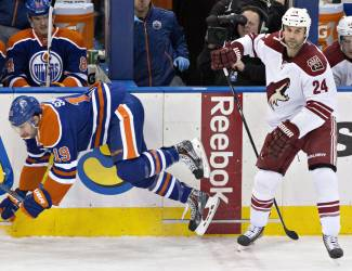 Arizona Coyotes' Kyle Chipchura (24) checks Edmonton Oilers' Justin Schultz (19) during the second period of an NHL hockey game in Edmonton, Alberta, Tuesday, Dec. 23, 2014. (AP Photo/The Canadian Press, Jason Franson)