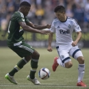Vancouver Whitecaps FC's Nicolas Mezquida, right, fights for control of the ball with Portland Timbers Alvas Powell during the first half of a MLS soccer match, Saturday, March 28, 2015 in Vancouver, British, Columbia. (AP Photo/The Canadian Press, Jonathan Hayward)