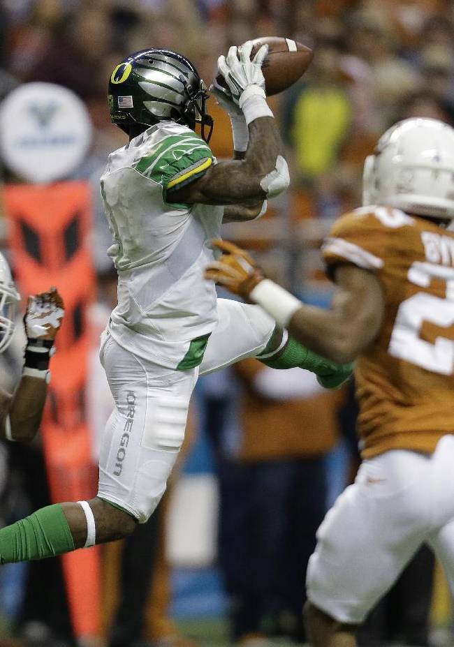 Oregon's Josh Huff, center, pulls in a pass as Texas' Quandre Diggs (6) defends during the second half of the Valero Alamo Bowl NCAA college football game, Monday,  Dec. 30, 2013, in San Antonio. Oregon won 30-7
