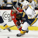 Chicago Blackhawks left wing Patrick Sharp (10) battles Nashville Predators defenseman Roman Josi (59) during the second period of an NHL hockey game on Saturday, Oct. 18, 2014, in Chicago The Associated Press