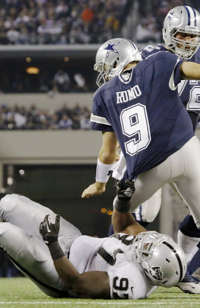 Oakland Raiders defensive tackle Daniel Muir (97) brings down Dallas Cowboys quarterback Tony Romo (9) during the second half of an NFL football game, Thursday, Nov. 28, 2013, in Arlington, Texas