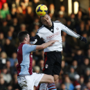 Fulham's Dimitar Berbatov, right, competes with Aston Villa's Claran Clark during their English Premier League soccer match at Craven Cottage, London, Sunday, Dec. 8, 2013