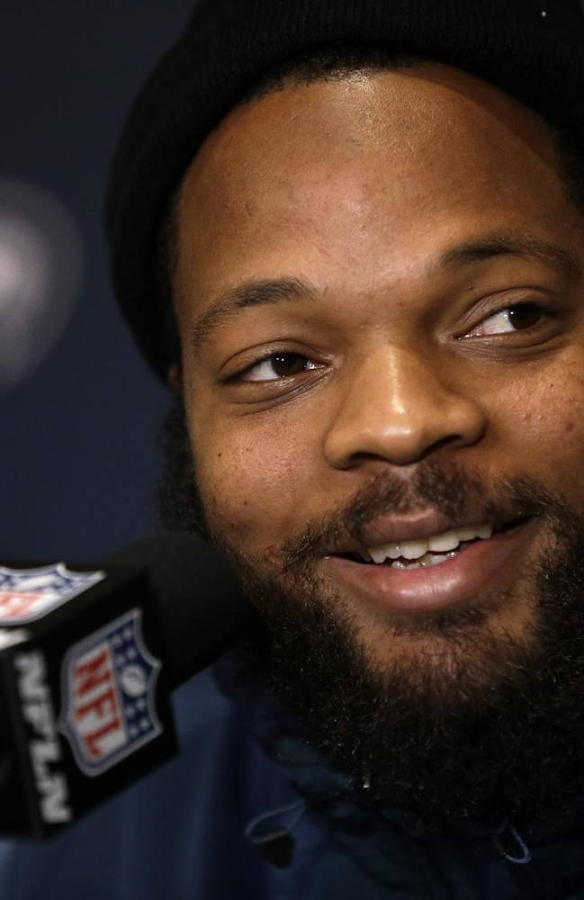 In this Jan. 27, 2014 file photo, Seattle Seahawks defensive end Michael Bennett smiles as he listens to a question during a news conference in Jersey City, N.J. NFL free agency begins Tuesday, March 11, 2014, with each team having another $10 million or so to spend thanks to the increased salary cap. Such standouts as receivers Eric Decker and Julian Edelman, defensive end Michael Bennett and cornerback Alterraun Verner figure to draw quick attention