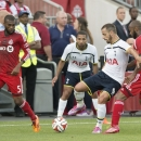 Tottenham Hotspur's Roberto Soldado, second from right, controls the battle in front of Toronto FC's Ashtone Morgan, left, and Collen Warner during the first half of a friendly soccer match in Toronto on Wednesday, July 23, 2014
