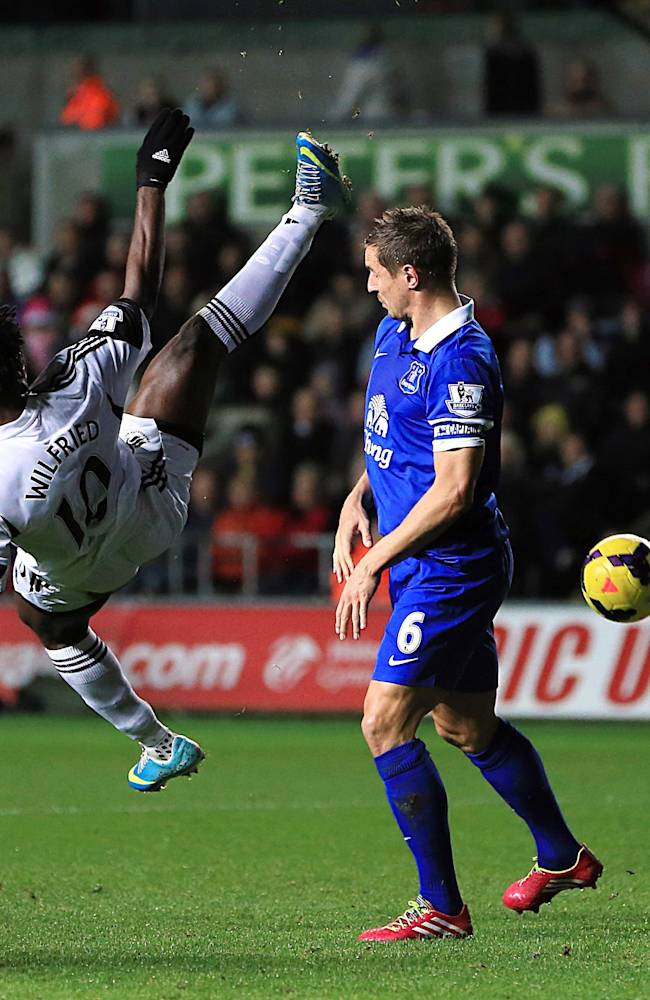 Everton's Phil Jagielka, right, and Swansea City's Wilfried Bony battle for the ball during their English Premier League soccer match at the Liberty Stadium, Swansea, Wales, Sunday, Dec. 22, 2013