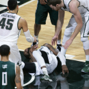 Michigan State's Branden Dawson lies on the court after going down with an injury between teammates Denzel Valentine (45) and Matt Costello during the second half of an NCAA college basketball game against Eastern Michigan, Wednesday, Dec. 17, 2014, in East Lansing, Mich. Michigan State won 66-46. (AP Photo/Al Goldis)