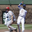Chicago Cubs second baseman Emilio Bonifacio, right, looks to first base after forcing out Cincinnati Reds' Ryan Ludwick during the second inning of a baseball game in Chicago, Friday, April 18, 2014. Devin Mesoraco was safe at first The Associated Press