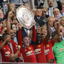Manchester United's Wayne Rooney holds the trophy after Manchester won the Community Shield soccer match against Leicester City, at Wembley stadium in London, Sunday, Aug. 7, 2016 . (AP Photo/Frank Augstein)