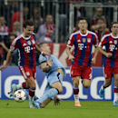 Bayern's Mario Goetze, left, and Manchester City's Edin Dzeko, 2. from left, challenge for the ball as Bayern's Robert Lewandowski, 2. from right, and Bayern's Philipp Lahm, right, look on during the Champions League Group E soccer match between FC Bayern
