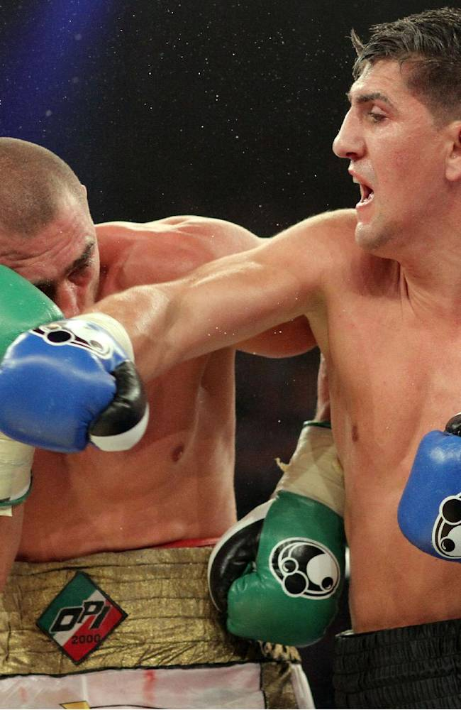 In  this picture taken Saturday Aug. 30, 2014 German boxer Marco Huck, right, sends a punch to Italian challenger Mirko Larghetti during their WBO cruiserweight title bout in Halle, western Germany.  German defending cruiserweight champion  Marco Huck defeated Mirko Larghetti of Italy by unanimous decision Saturday to retain his WBO belt for the record-equaling 13th time