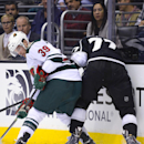 The puck pops out as Minnesota Wild defenseman Nate Prosser (39) and Los Angeles Kings center Jeff Carter (77) fight for it during the second period of an NHL hockey game, Monday, March 31, 2014, in Los Angeles The Associated Press
