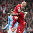 Liverpool's Martin Skrtel, top, celebrates with teammate Glen Johnson as his team beat Manchester City 3-2 during their English Premier League soccer match at Anfield Stadium, Liverpool, England, Sunday April 13, 2014