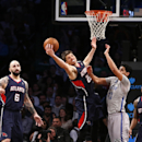 Atlanta Hawks' Kyle Korver, center, grabs a rebound against the Brooklyn Nets late in the fourth quarter of an NBA basketball game Friday, April 11, 2014, in New York. Atlanta won 93-88 The Associated Press