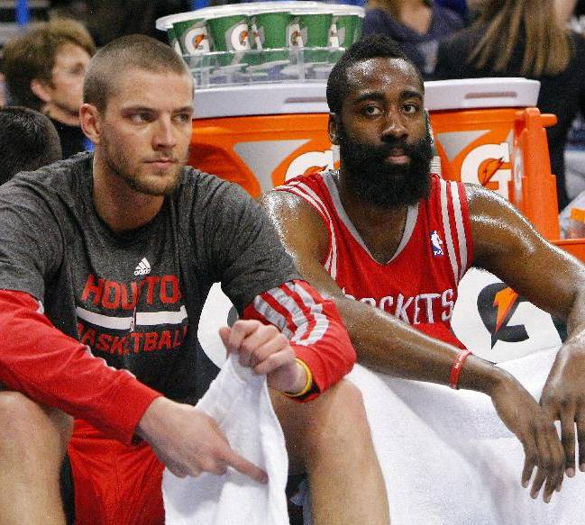 Houston Rockets forward Chandler Parsons, left, and guard James Harden, right, sit on the bench during the fourth quarter against Oklahoma City Thunder during an NBA basketball game, Sunday, Dec. 29, 2013, in Oklahoma City. Oklahoma City won 117-86